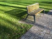 Lavička v parku vrhající dlouhý stín
