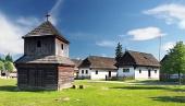 Dřevěná zvonice a lidové domy ve skanzenu Pribylina na Slovensku