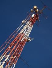 Červeno bílý rádiový vysílač na pozadí s modrou oblohou