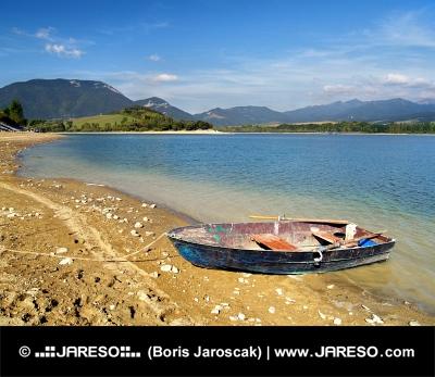 Malá loďka částečně vytažena na břehu