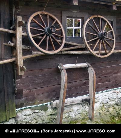 Stěna dřevěnice s tradičními venkovskými nástroji